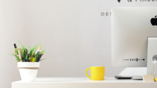 マッキントッシュとコーヒーカップが載ったオフィスのデスク