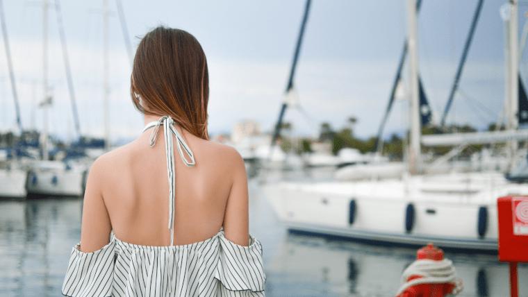 背中の大きく開いた服を着て海辺に立つ女性