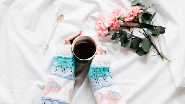 長袖を着てコーヒーカップを持つ女性の手