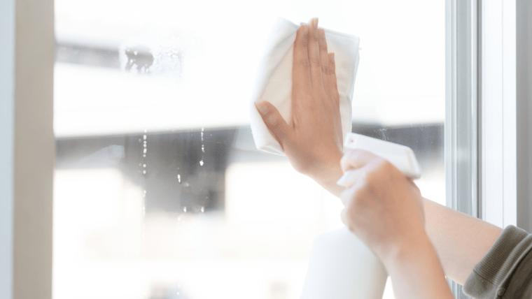 窓ガラスを拭き掃除する人の腕