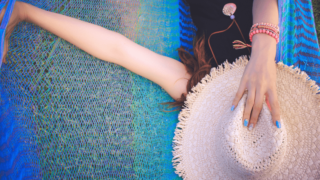 帽子で顔を隠してハンモックで寝る女の子