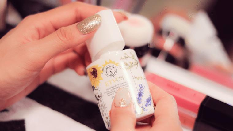 UV化粧品のボトルのキャップを開ける女の子の手