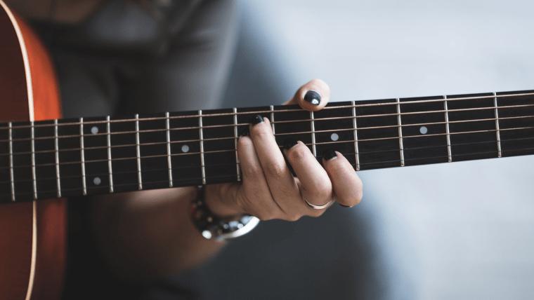アコースティックギターを弾く女性の手元