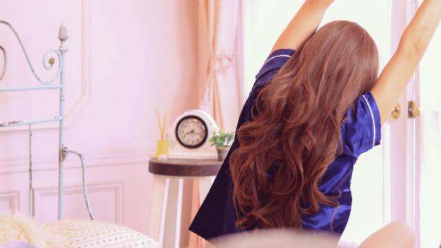 朝ベッドの上で伸びをする女の子