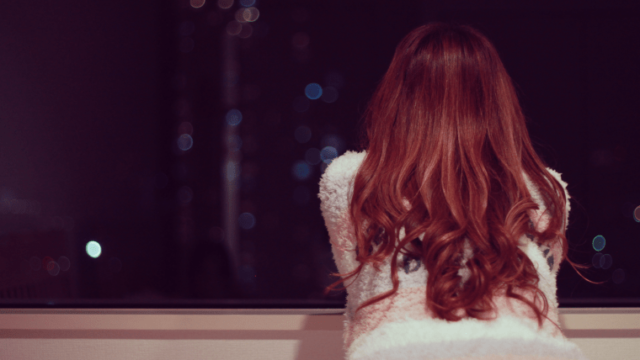 窓から夜景を眺める女の子
