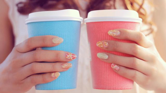 コーヒーの紙カップを両手に持つ女の子