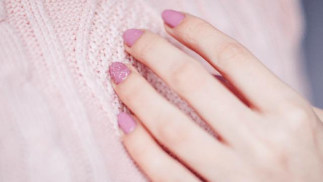 ピンクのマニキュアをした女性の指先
