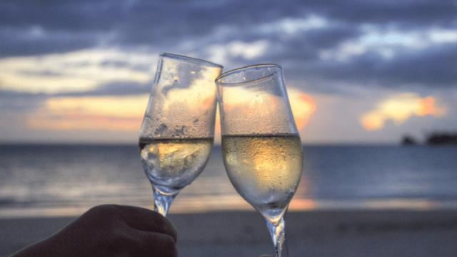 海辺でシャンパングラスで乾杯するふたり